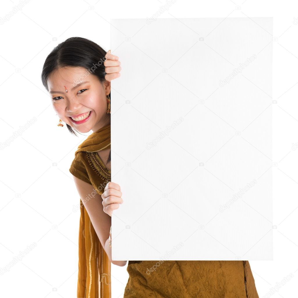 edc4308c99 Portrait of young mixed race Indian Chinese girl in traditional punjabi  dress hiding behind a blank white paper card, standing isolated on white  background.