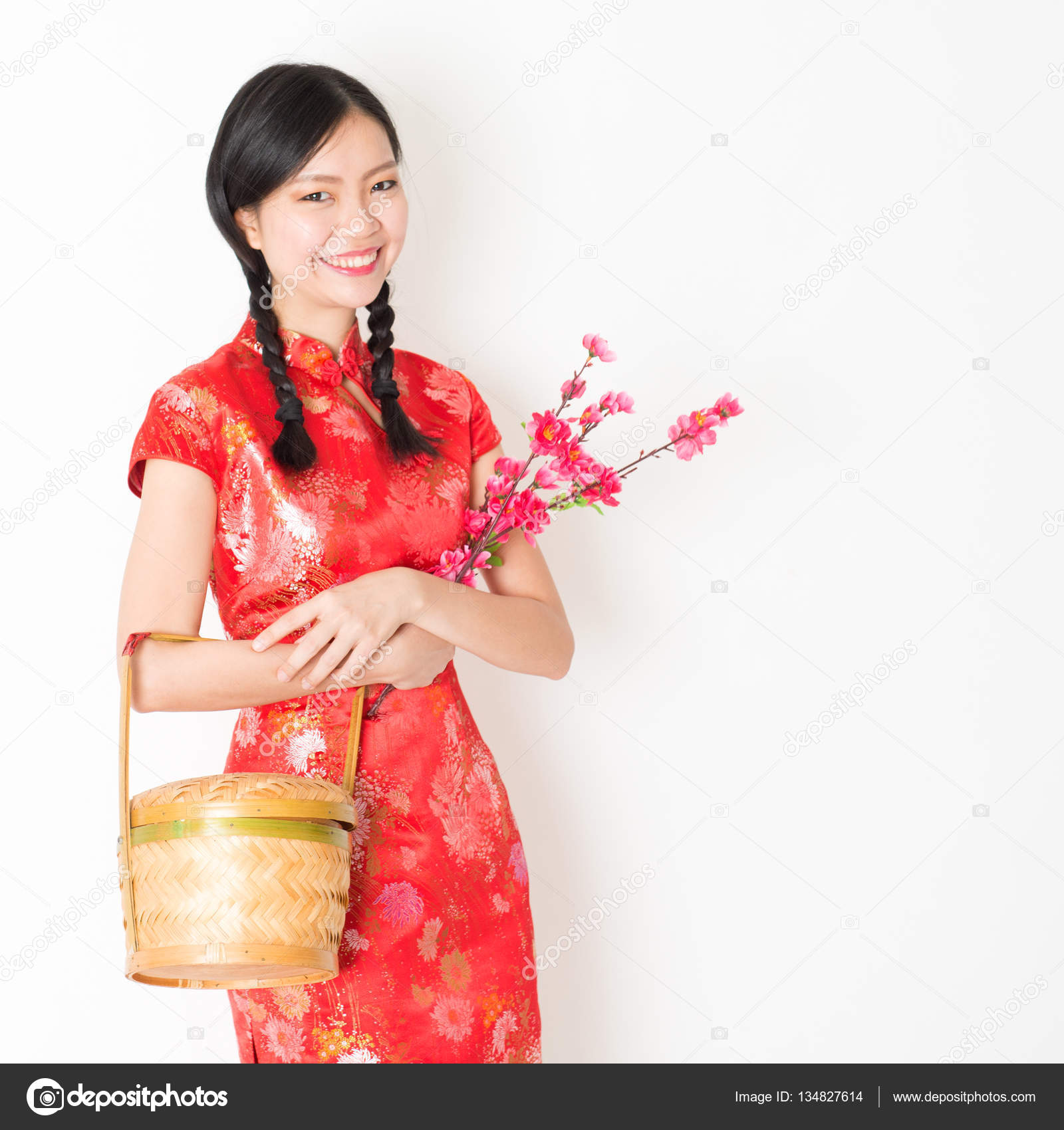 383349162 Young Asian woman in traditional cheongsam dress holding gift basket and  plum blossom smiling, celebrating Chinese Lunar New Year or spring festival,  ...