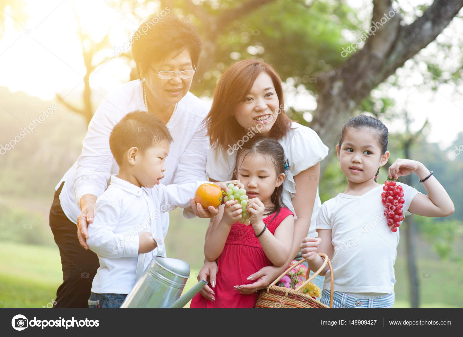 21d13228a8f Αυθεντικές πορτρέτο της χαρούμενη πολλαπλών γενεών ασιατικής οικογένειας  στο πάρκο. Γιαγιά, μητέρα και εγγόνια υπαίθρια διασκέδαση. Το πρωί ήλιος  φωτοβολίδα ...