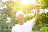 asiatische alte Mann spielen Hantel in den Park