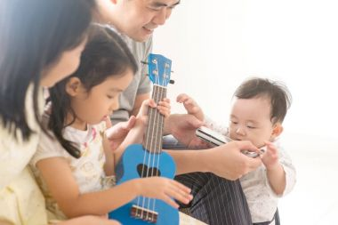 Family playing ukulele and harmonica at home