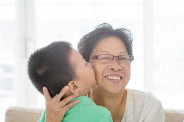 Grandchild kissing grandmother