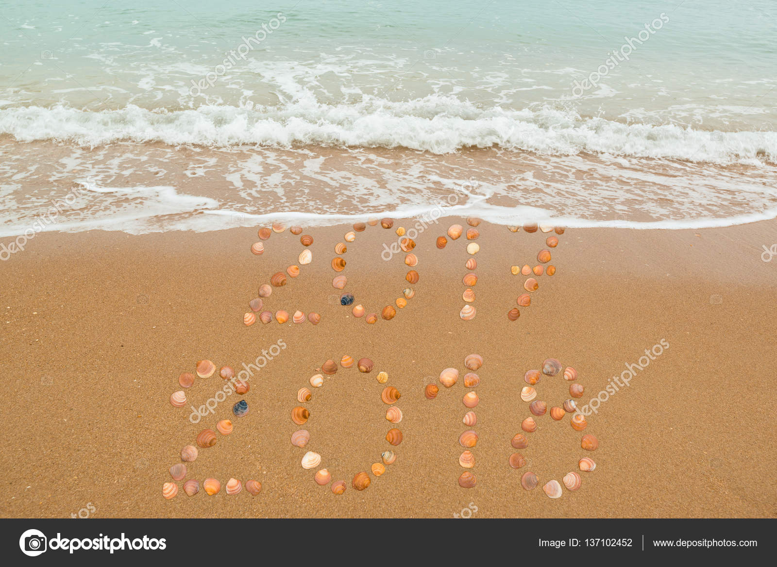 happy new year 2018 concept the waves are about to cover 2017 both years placed with seashells on the beach photo by franky242