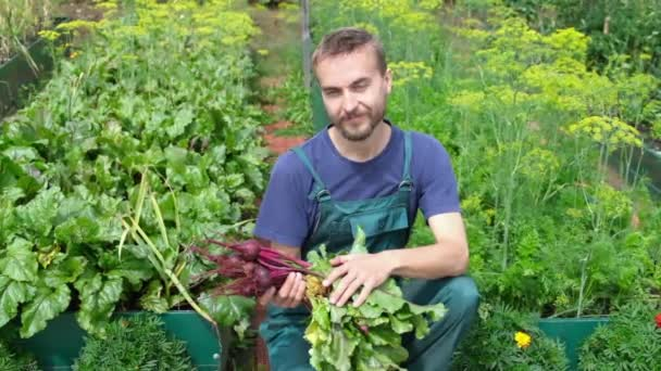 Portrait of young cheerful farmer with freshly harvested beet crop sitting among vegetable beds. Male gardener harvest bio veggie in local organic garden. Sustainable food.