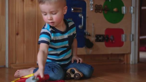 Roztomilý batole chlapeček hrající si s hračkami ve školce, ve školce nebo v herně. Běloch opravuje dřevěné auto pomocí hraček. Malý mechanik.