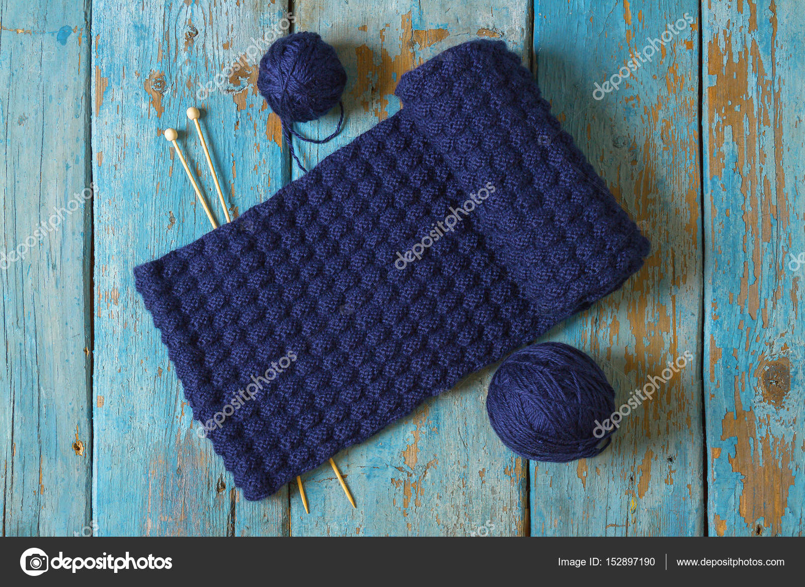 Dos bobinas de lana, agujas de tejer y una bufanda de punto azul ...