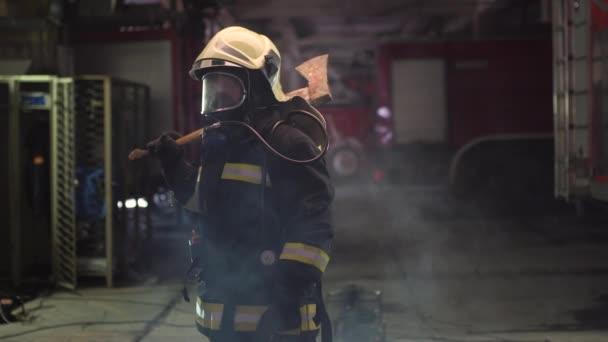ženský hasičský portrét s plnou výbavou, kyslíkovou maskou a sekerou, kouřem a hasičskými vozy v pozadí.