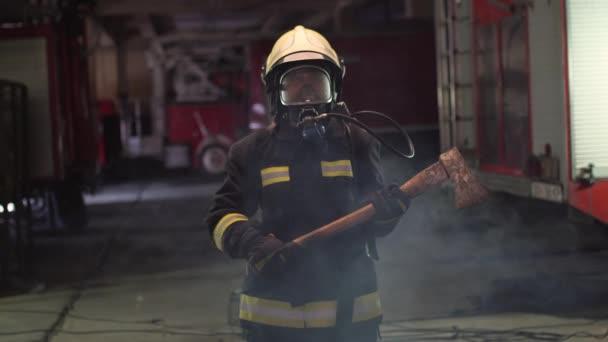 portrét ženského hasiče s plnou výstrojí, kyslíkovou maskou a sekerou. kouř a hasičské vozy v pozadí.