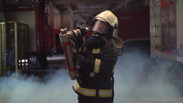 ženský hasičský portrét s plnou výbavou, kyslíkovou maskou a nouzovým záchranným vybavením, tvrdým nářadím, kouřem a hasičskými vozy v pozadí.