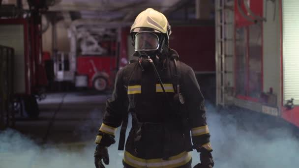 Hasičský portrét s plnou výbavou, kyslíkovou maskou a nouzovým záchranným vybavením, hydraulickými svorkami, kouřovými a požárními vozy v pozadí.