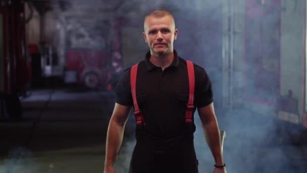 portrét hasiče v košili a kalhotách, se sekerou, kouřem a hasičskými vozy v pozadí.