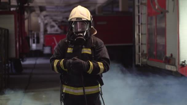 Portrét hasiče v plné výbavě. Nasazuju si kyslíkovou masku. Kouř a hasičské vozy v pozadí. Překlad jmenovky je hasič a příjmení modelu.