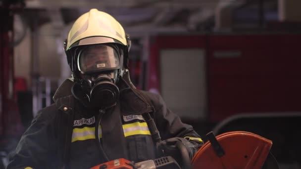 Hasičský portrét s plnou výbavou, kyslíkovou maskou a elektrickým hydraulickým řezacím nářadím, kouřovými a požárními vozy v pozadí. Překlad jmenovky je hasič a příjmení modelu.