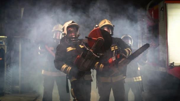 skupina hasičů s plnou výstrojí, kyslíkovými maskami a nouzovým záchranným nářadím, kruhovou hydraulickou a plynovou pilou, sekerou a kladivem. kouř a hasičské vozy v pozadí.