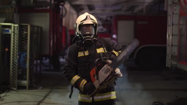 Hasičský portrét s plnou výbavou, kyslíkovou maskou a motorovou pilou. Kouř a hasičské vozy v pozadí.