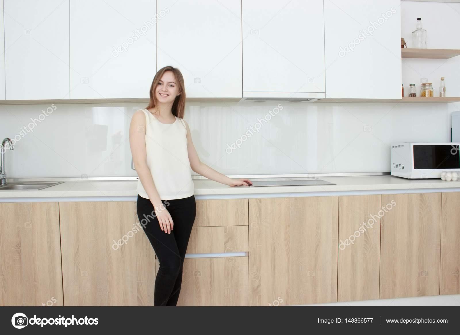 Bastante joven mujer en una camiseta blanca de pie en la cocina y ...