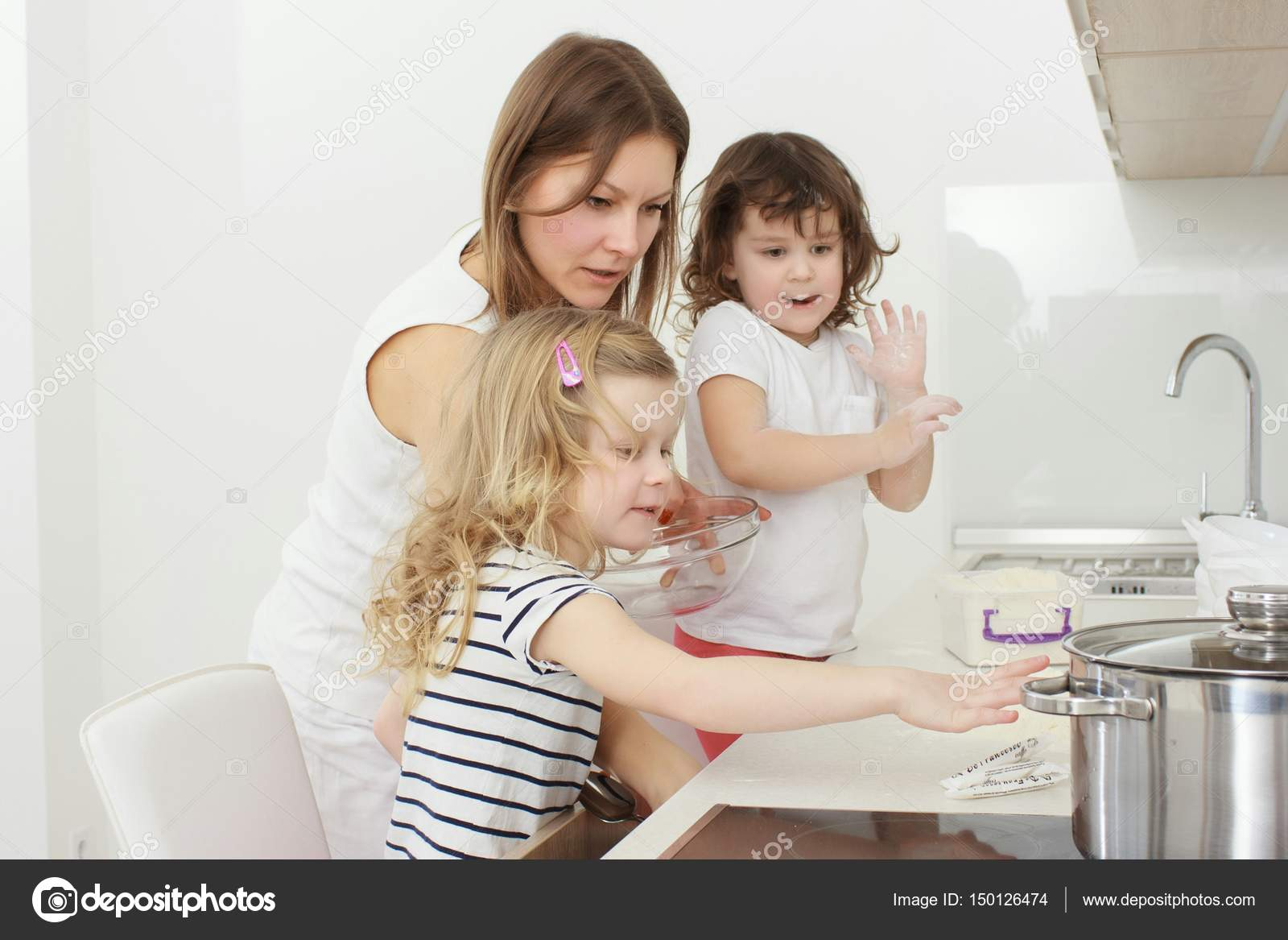 Mother with her 5 years old kids cooking holiday pie in the kitchen ...