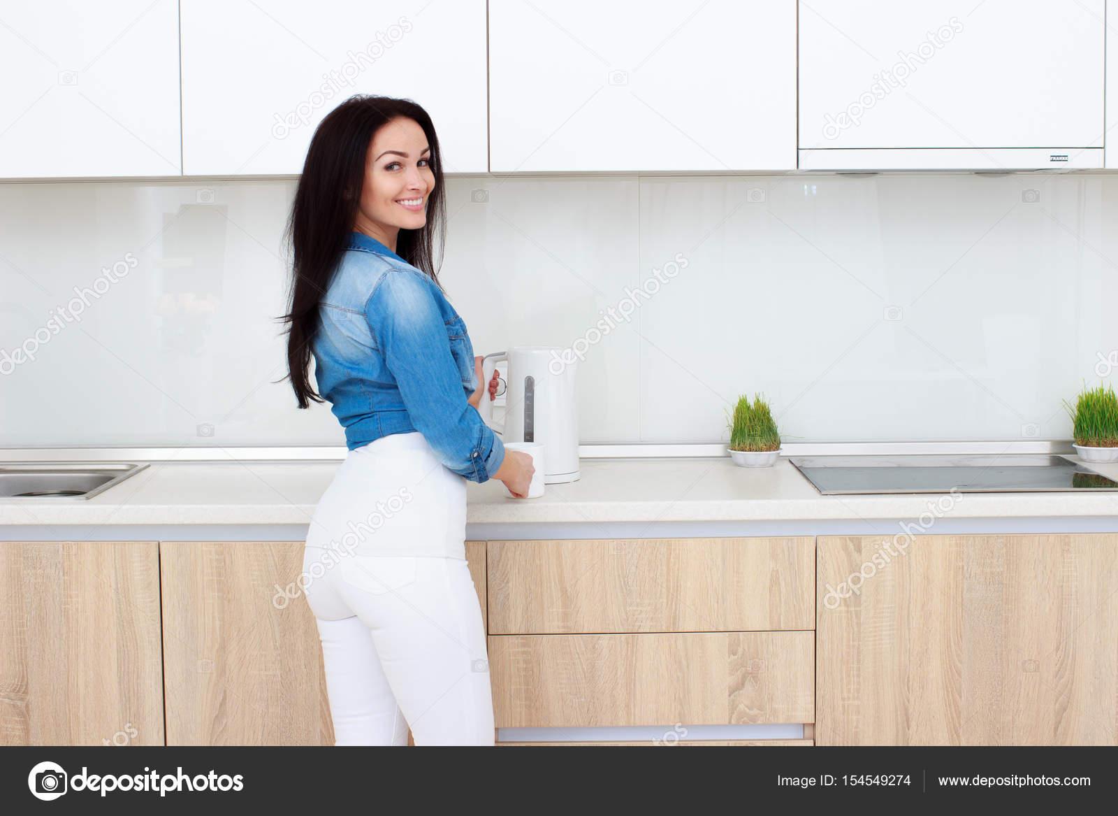 Volwassen brunette avrouw thee op kamer keuken interieur