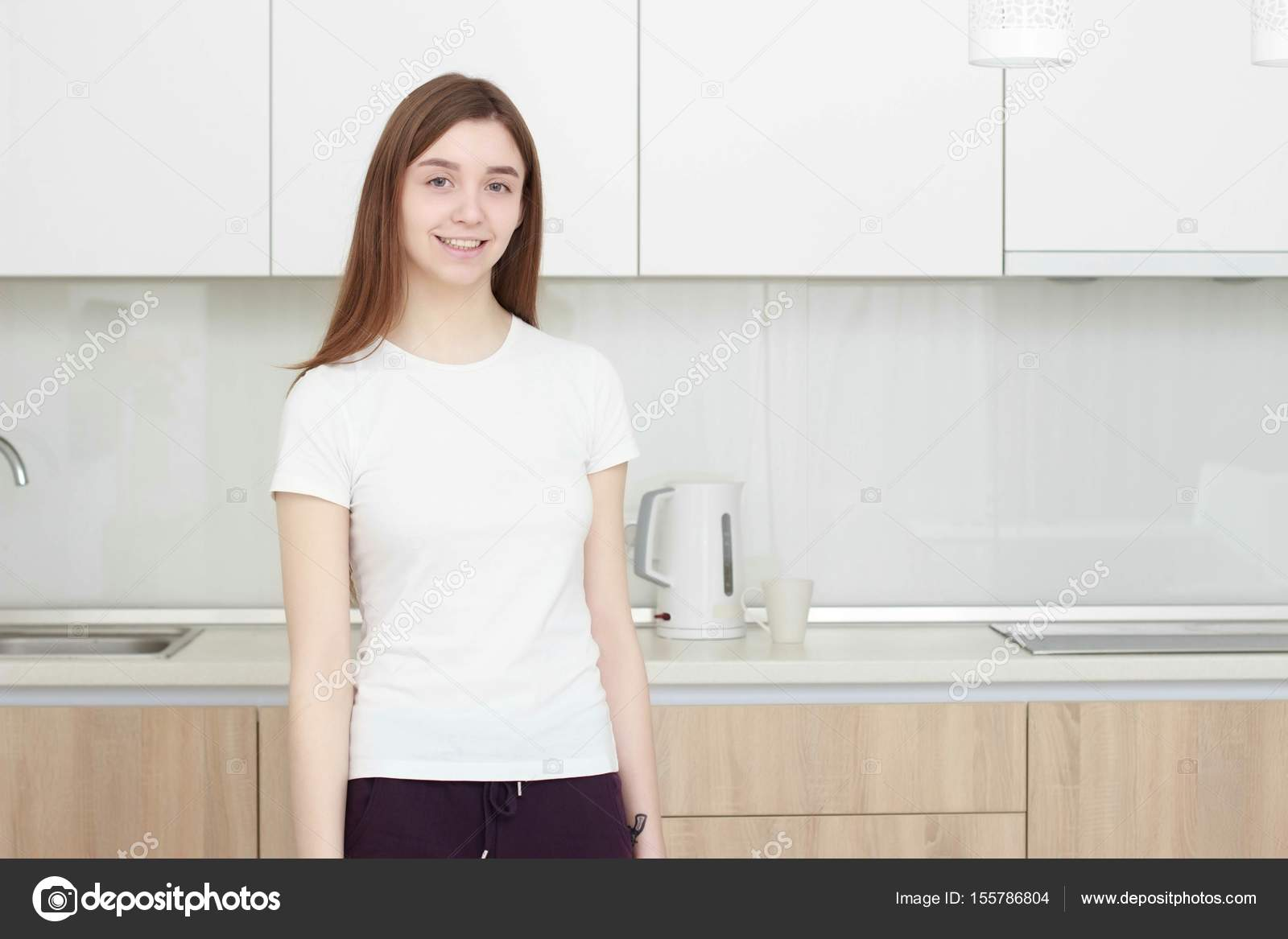Pretty young woman In a white T shirt standing in kitchen and ...