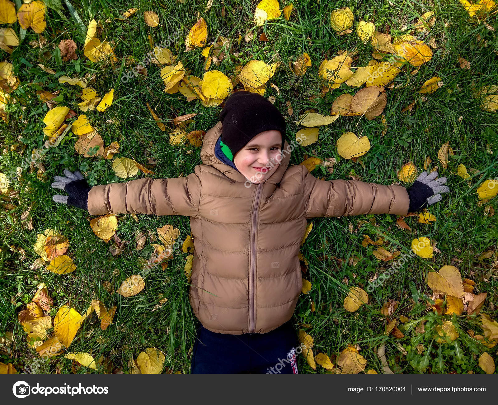 foto de Cheerful 4 years old boy lying on yellow leaves in autumn