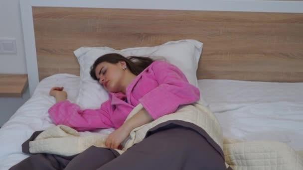 Mladá žena spí v posteli, noční můry a pohybující se ve spánku