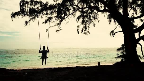 Muž na Swing zablokuje a strom na tropické pláži. Letní prázdniny a dovolené koncepce