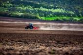 Farmář s traktorem setí plodin na poli