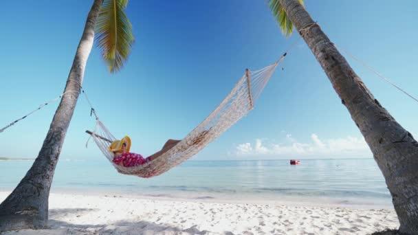 Holčička odpočívanou v houpací síti na tropické ostrovní pláži. Letní prázdniny v Punta Cana, Dominikánská republika