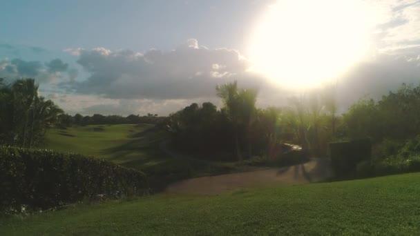 Golfové hřiště v luxusním tropickém resortu. Západ slunce nad sportovními poli, pozemky a palmami.