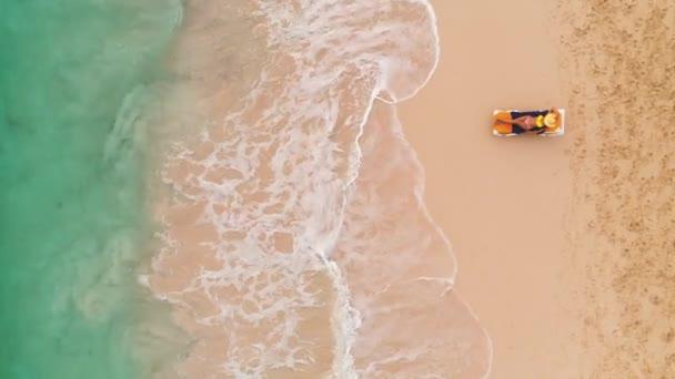 Dovolená na pláži v ráji tropického ostrova, sexy opálená žena relaxující na pláži a na moři. Letecký pohled shora.