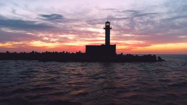 Silueta majáku na moři při západu slunce