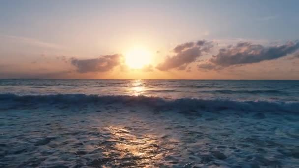 golden sea sunrise and splashing waves on the sand, aerial view