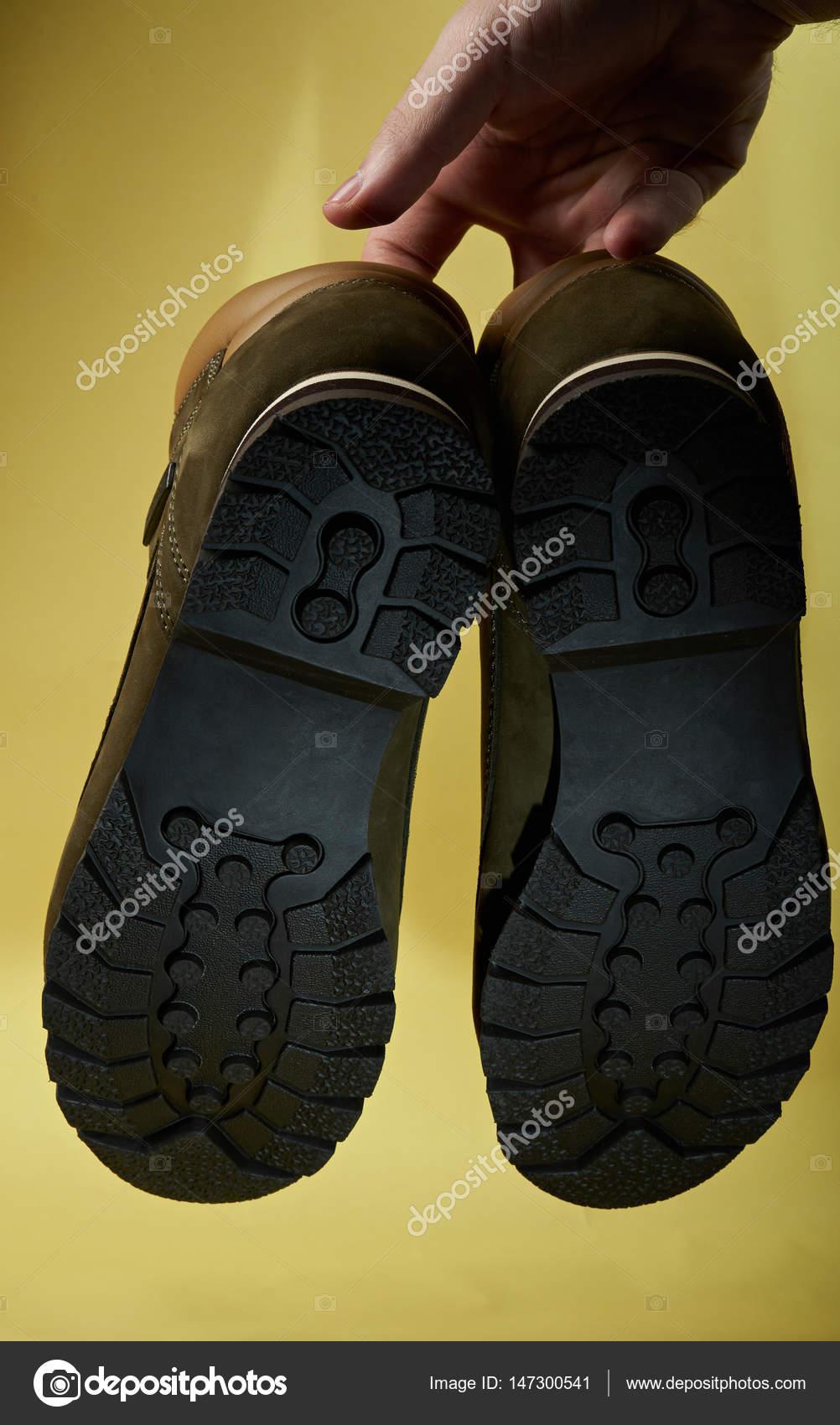 Κάτω μέρος του τα παπούτσια πεζοπορίας που κρέμονται από πλευρά  απομονώνονται σε κίτρινο φόντο — Εικόνα από dimarik a7b7dc87398