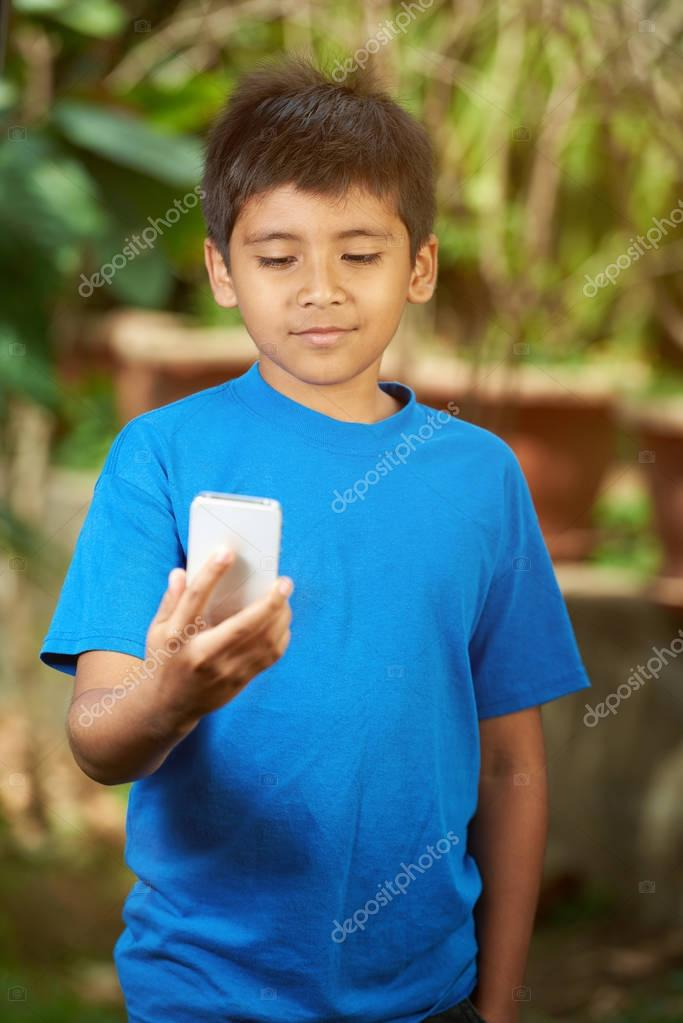 Small boy look into smartphone
