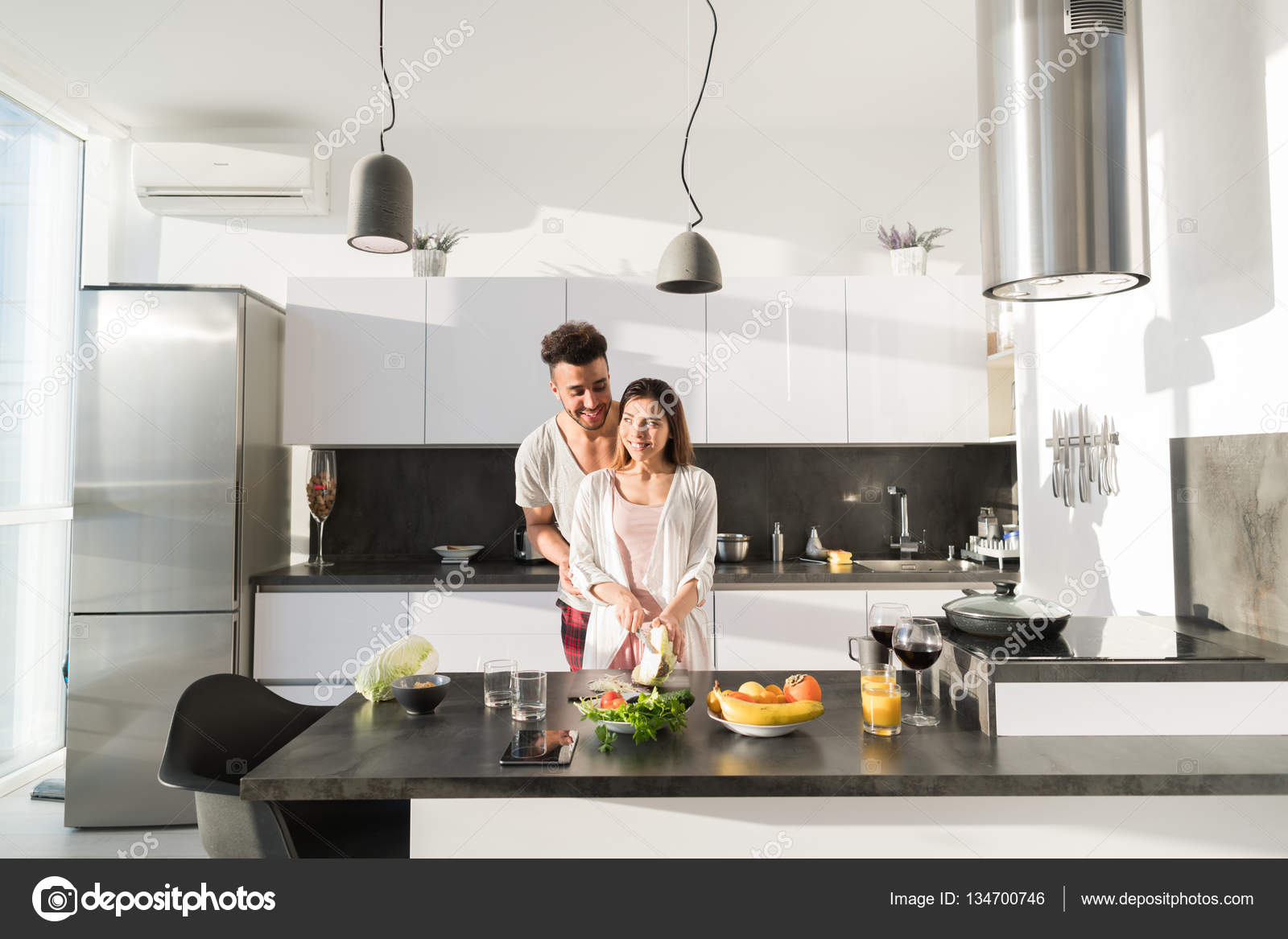 Young Couple Embrace In Kitchen, Hispanic Man And Asian Woman Hug ...