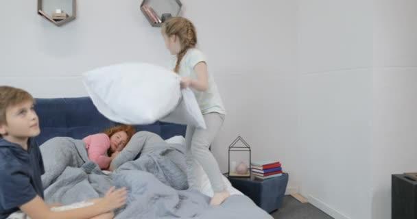 Děti s polštáři bojovat na posteli s rodiči, ráno šťastná rodina v ložnici na spaní