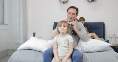 Father Putting New Headphones On Little Daughter Listening To Music Through Headset While Spending Time In Bedroom With Happy Family