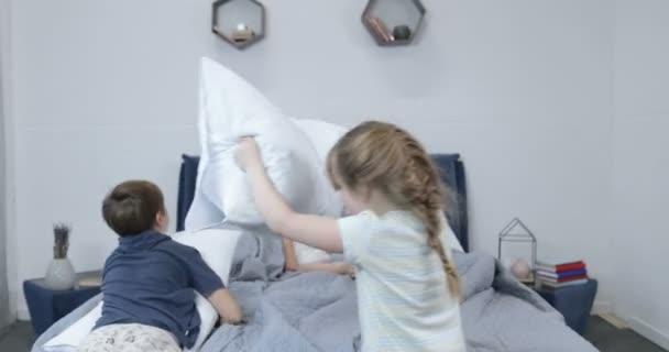 De bestrijding van de kinderen met kussens op bed van de ouders