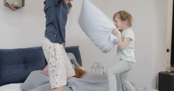 Gelukkige kinderen plezier in ouders slaapkamer vechten kussens in