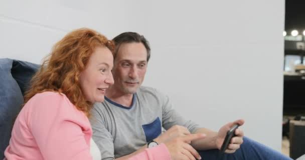 Dospělý pár použití chytrý mobil, ležící v posteli nad děti hrají spolu rodinu v ložnici