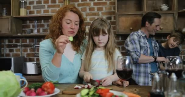 Matka a dcera, sekání zeleniny, zatímco otec se synem pomocí tabletového počítače, šťastná rodina, společné vaření v Fitchen doma
