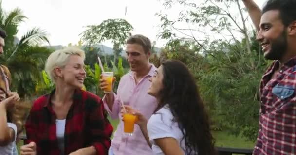 junge Leute tanzen beim Kochen Grillen fröhliche Gruppe fröhliches Treffen auf der Sommerterrasse mit Party