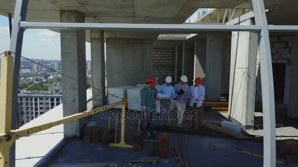 Letecká zadní zadní pohled skupiny stavitelé na staveništi, inženýři v budově objektu diskutuje plán projektu