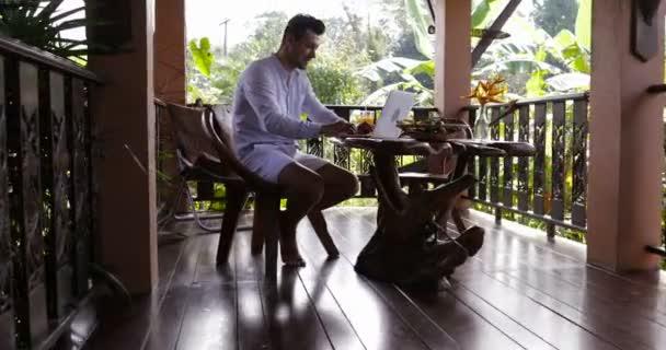 Příležitostné obchodní muž pracuje na přenosném počítači posezení venku na terase v pralesy během snídaně, mladý kluk, psaní