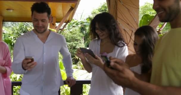 Skupina lidí s chytré mobily konverzujete, Mix závod mužů a žen na letní terase zasílání zpráv