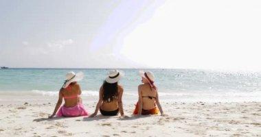 Vissza a hátsó nézet három lány a strandon a Bikini, élvezni a Sun Tan beszél, a nő levette szalmakalappal turisták a nyári szünet