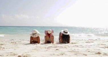 Vissza a hátsó nézet három lány feküdt, strandon, lábak, emelés, élvezze a Sun Tan, nő a turisták a nyári szünet
