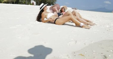 Három lány feküdt, strandon a Bikini és a szalma kalap, élvezze a Sun Tan beszél, boldog asszony turisták, Nyári nyaralás