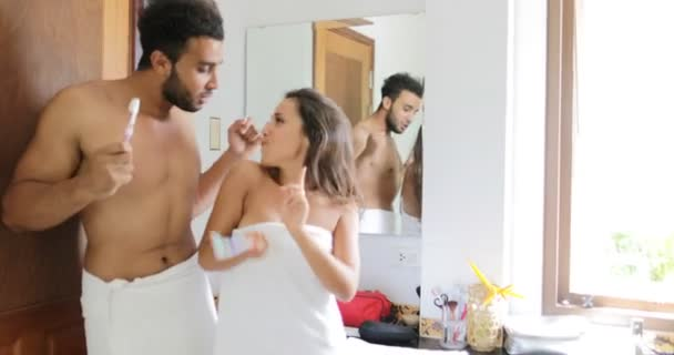 Pár čištění zubů v koupelně, tanec veselý muž a žena spokojený úsměv dělá ranní hygiena