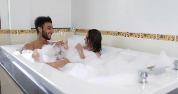 Mladý pár relaxaci v lázni společně šampaňské, muž a žena milence si lázně doma